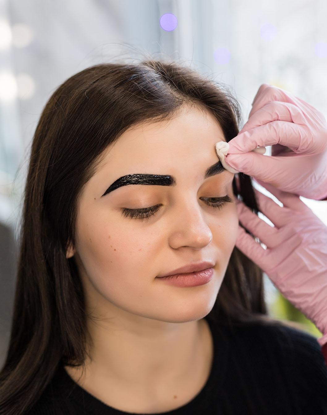 master doing final steps in make-up procedure in salon